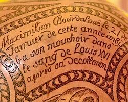Une partie de la calebasse qui mentionne les circonstances dans lesquelles le sang de Louis XVI a été récupéré. Crédits photo: Davide Pettener
