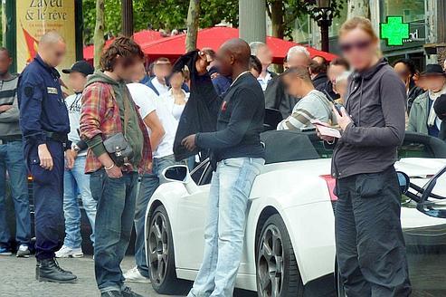Sur les Champs-Élysées, des membres du GIR contrôlent le conducteur d'une voiture de luxe.