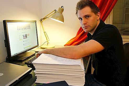 Max Schrems pose devant son dossier personnel Facebook (1200 pages).