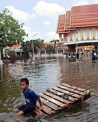Ce jeune garçon utilise une palette pour se déplacer hier dans la capitale inondée et vidée de la plupart de ses habitants.