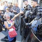 Une manifestante pointe avec humour le dispositif policier.