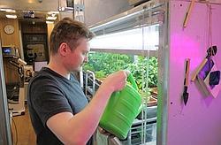 Un des astronautes en train d'arroser des plantes.