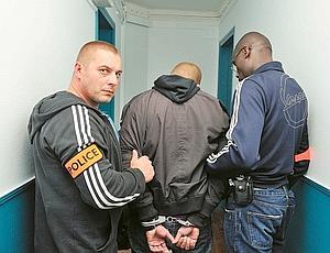 Menottes aux poignets, un membre d'un gang de dealers est placé en garde à vue. La BAC a saisi 60 kg de drogue. (Jean-Pierre Rey)
