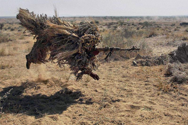 <b>Sniper sauteur.</b> À l'exercice, ce sniper de l'armée indienne se jette sur le sol avant de prendre position. En tenue de camouflage, il rejoint ainsi son coéquipier déjà prêt à faire feu à sa gauche. Une manœuvre organisée dans le Rajasthan, non loin de la frontière avec le Pakistan. C'est l'occasion d'essayer sur le terrain leur nouvel uniforme, un tiers rasta, un tiers poil de briard, un tiers vieille serpillière. Toutefois, en dépit du ridicule apparent de leur tenue, ces tireurs d'élite utilisent Le même dispositif que les armées du monde entier. Cet assemblage de tissus, adaptable à tous les terrains, constitue actuellement le meilleur camouflage au monde. Même les drones s'y perdent.