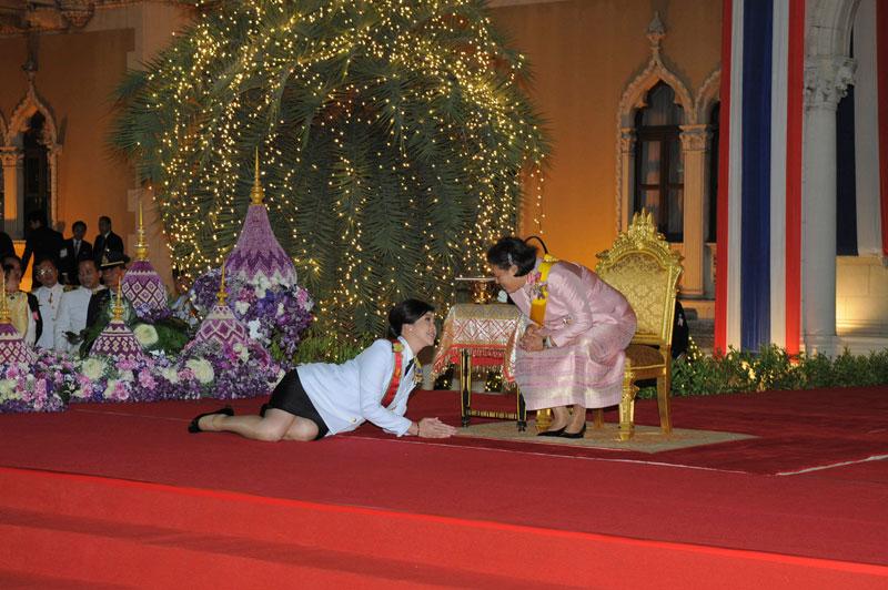 <b>Message thaïlandais</b>.Allongée, les mains jointes en signe de profond respect, Yingluck Shinawatra, Premier ministre thaïlandais, rend hommage à la princesse Maha Chakri Sirindhorn, à l'occasion de l'anniversaire du roi Bhumibol Adulyadej. Une scène ahurissante qui en dit long sur le protocole de la monarchie et le culte dont la famille royale fait l'objet. Âgé de 84 ans et sur le trône depuis 65 ans, le roi de Thaïlande, le plus ancien monarque en exercice dans le monde, est considéré comme un véritable demi-dieu. Comme les autres membres de sa famille, qui n'ont aucune prérogative constitutionnelle, mais exercent une très forte autorité morale. Tout comme le comité chargé de la répression contre les crimes de lèse majesté.