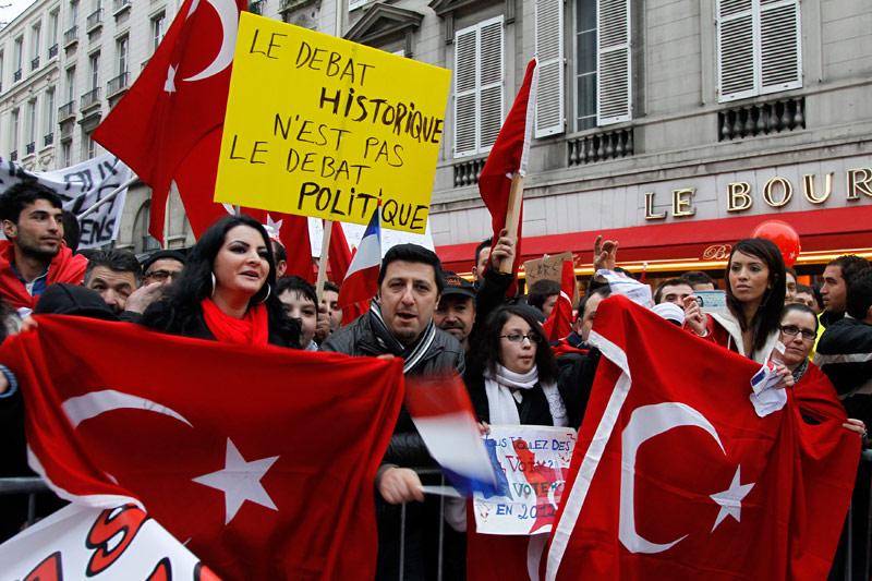 Manifestation. La tension monte entre la France et la Turquie. Environ 3000 manifestants s'étaient donné rendez-vous ce jeudi devant l'Assemblée nationale, alors que la Turquie a rappelé son ambassadeur en poste à Paris, jeudi 22 décembre, peu de temps après l'adoption d'une proposition de loi sur la négation des génocides, dont celui des Arméniens en 1915. Tahsin Burcuoglu ''part demain'' vendredi, a confirmé le porte-parole de l'ambassade, Engin Solakoglu, et le premier ministre turc devrait préciser sous peu la nature des décisions prises par Ankara. La Turquie avait prévenu qu'il y aurait des conséquences graves en cas d'adoption de ce texte. Le ministre des affaires étrangères Ahmet Davutoglu avait déclaré au Monde qu'il s'agissait d'une ''attaque contre notre dignité nationale''. Après les sanctions diplomatiques, des mesures économiques, voire culturelles sont à prévoir.