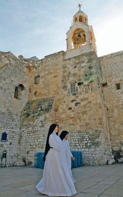Deux nonnes traversent la place de la Mangeoire devant la basilique de la Nativité à Bethléem.