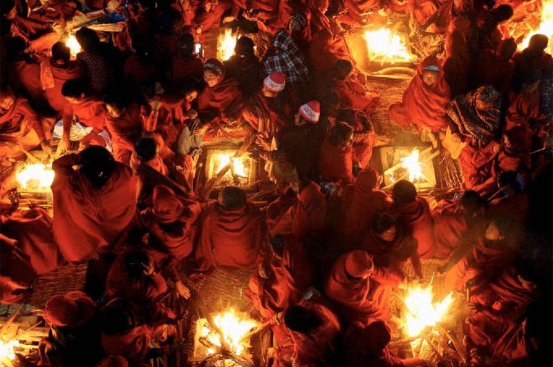 <b>Feux sacrés</b>. Ces paysannes népalaises, rassemblées autour de braseros carrés, composent à leur insu une superbe mosaïque de rires et de ferveur. Elles se réchauffent en attendant l'aube du 9 janvier, premier jour du mois sacré de Magh, où les hindouistes népalais (87%de la population) célèbrent aussi la fin du mois de Poush, celui des mauvais présages. Dans quelques heures, ces adoratrices de Vishnou s'immergeront dans la rivière Saali, avant d'entamer tout un mois de réjouissances religieuses. Un bain moins frigorifiant qu'on pourrait le croire ; car le 9 janvier a beau être considéré au Népal comme «le jour le plus froid de l'année», sa température dans la vallée de Katmandou descend rarement en dessous de 15 °C.