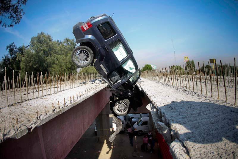 <b>De justesse.</b> En équilibre, cette voiture suspendue entre les deux épais tabliers d'un pont en construction dans la ville de Mexico City témoigne de la violence du choc. Son conducteur, qui roulait trop vite, a rapidement perdu le contrôle de son véhicule qui est brutalement sorti de route.