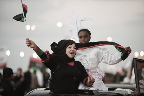 Des femmes brandissent le nouveau drapeau libyen pour commémorer le premier anniversaire de la révolution, à Benghazi.