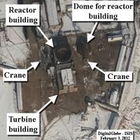 Le bâtiment de la turbine apparaît terminé, mais pas le bâtiment du réacteur, dont le dôme est encore au sol, près d'une grue («crane» en anglais).