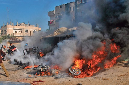 Des Palestiniens tentent d'éteindre un feu dans une rue de Rafah, dans le sud de la bande de Gaza, samedi, après une attaque aérienne des Israéliens.