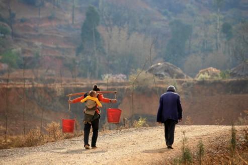 Une Chinoise de la province de Yunnan transporte de l'eau, avec son enfant sur le dos.
