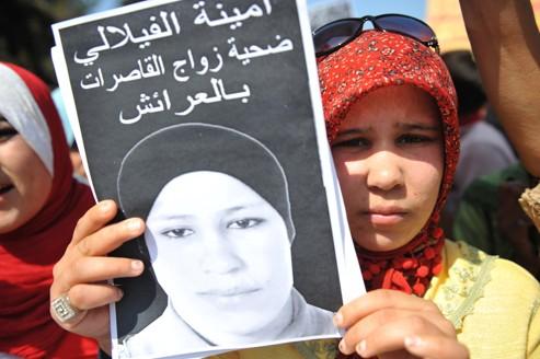 Une jeune fille tient une photo d'Amina lors d'une manifestation à Larache.
