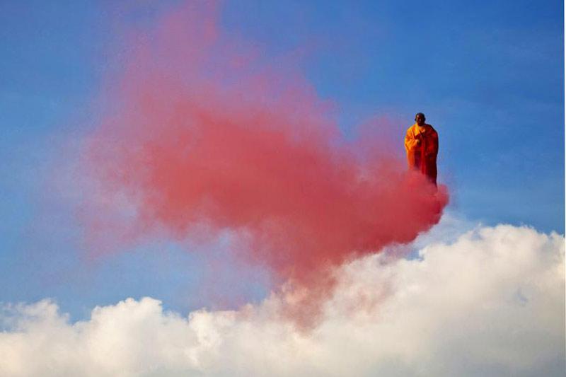 <b>Moine fumeux.</b> En prière dans un état de conscience hors du commun, ce moine bouddhiste en lévitation transcendantale a réussi l'incroyable exploit de chevaucher un nuage rouge au beau milieu du ciel. Rouge comme le feu et la passion. Un miracle en somme. Sauf que sous la robe safran de ce curieux paroissien se cache l'artiste chinois Li Wei, et derrière le nuage, la plate-forme d'une grue qui le maintient dans les airs attaché par un harnais, juste au-dessus de la Fontaine aux lions du parc de la Villette à Paris. Dommage non? Reste cette intrigante fumée écarlate? Là encore, le maître en illusions d'optiques et en installations aériennes a trouvé une solution idéale: Li Wei a tout simplement attaché des feux de Bengale à ses chaussures. Une jolie fumisterie.