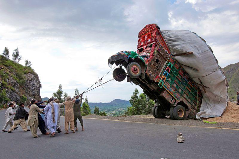 <strong>Rodéo mécanique.</strong> Ils sont plus d'une dizaine, mais arriveront-ils à remettre sur ses roues ce camion sur chargé? Jusqu'ici, pourtant, tout allait pour le mieux. Son chauffeur roulait tranquillement sur la route montagneuse de Dargai, dans le district pakistanais de Makaland, à environ 160 kilomètres d'Islamabad, la capitale. Il savait que, comme d'habitude, son patron avait chargé sa remorque de fourrage jusqu'à l'extrême limite. Mais cela ne l'inquiétait pas.AuPakistan, c'est souvent la règle. Les camions sont fatigués, les normes inexistantes, mais la science des «chargeurs» fait des miracles. Jusqu'à ce virage en épingle et cette marche arrière de trop quiaprovoqué l'accident bête: la chute en arrière… Et cette scène de rodéo mécanique faceàuncamion cabré.