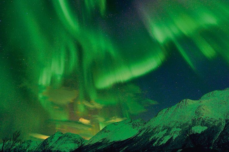 L'orage magnétique du 24 janvier 2012 déverse une pluie d'aurores qui irradie les parois du fjord à Tomso en Norvège.