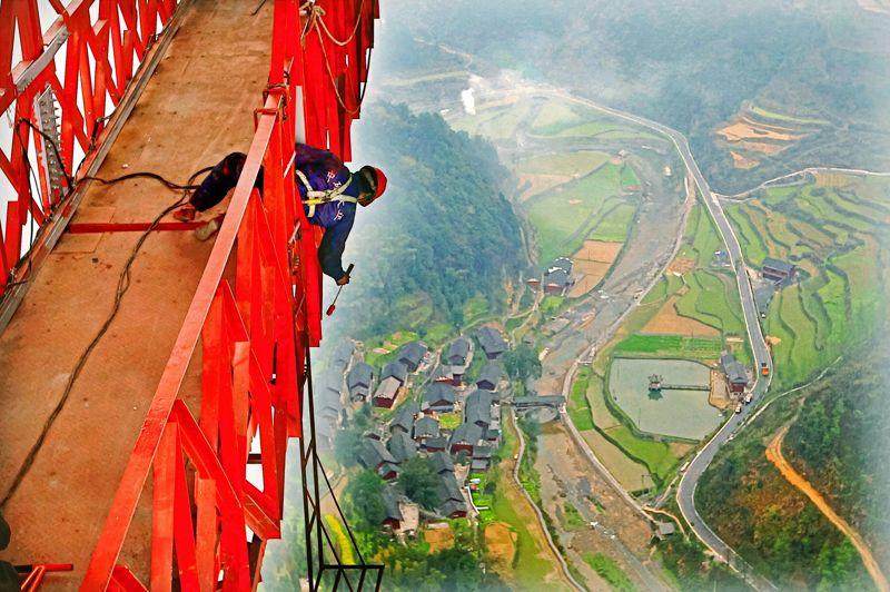 <strong>ACCROCHE-TOI AU PINCEAU!</strong> - Aucun trucage optique sur cette photo:si elle vous donne le vertige, c'est justifié. Car ce pont suspendu chinois, sur lequel un ouvrier encordé est en train de mettre une dernière touche de peinture, trois jours avant son inauguration, est désormais le plus haut et le plus long du monde. Jeté entre deux tunnels au dessus du canyon deDehang, dans la province centrale du Hunan, il permet de franchir une distance de 1,175 kilomètres à 335 mètres de hauteur, sans le moindre pilier pour le soutenir. La partie que l'on voit sur ce cliché est le trottoir réservé aux piétons, prudemment situé sous les deux fois deux voies de l'autoroute que voitures et camions sillonnent depuis le 3 avril à une vitesse maximale autorisée de 80 km/h.