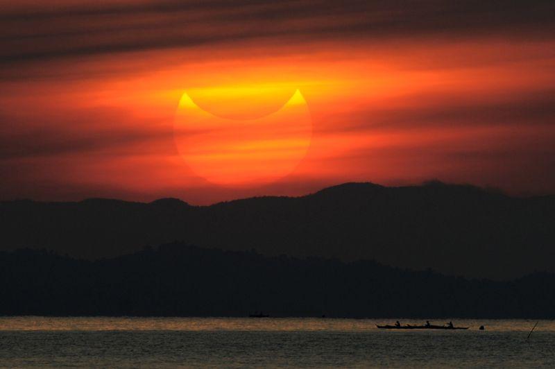 Le Soleil était déjà partiellement éclipsé par la Lune lorsqu'il s'est levé au-dessus des Philippines, ici dans la province de Quezon au sud-est de Manille.