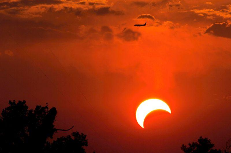 Passage d'un jet devant le Soleil partiellement éclipsé à Irving, au Texas.