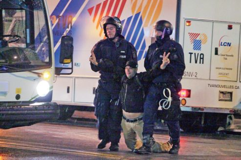 Des policiers arrêtent un étudiant lors d'une manifestation, mardi à Québec.