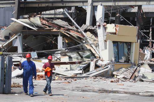 Des pompiers fouillent dans les décombres d'une usine détruite par le séisme de mardi, à Mirandola.