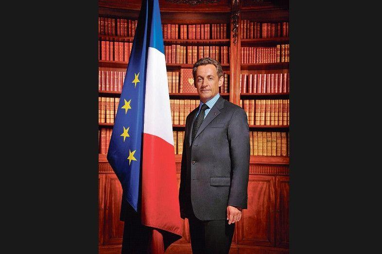 <strong>Nicolas Sarkozy, à l'américaine -</strong> D'avis unanime, ce portrait en pied du président Sarkozy, à côté d'un drapeau français trop grand et qui retombe comme la voile des marins au pot au noir, est une erreur de communication. Qui remarque les étoiles de l'Europe? Le cliché, pris en 2007, est l'œuvre d'un photographe people, Philippe Warrin, qui s'est distingué dans le «Loft» et la «Star Ac». La bibliothèque de l'Élysée, qui revient en leitmotiv, accentue l'académisme de la composition. Le visage jeune, loin des caricatures sauvages qui marqueront sa présidence, est perdu au loin.