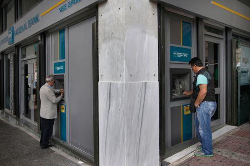Des Grecs retirent de l'argent à un guichet bancaire à Athènes.