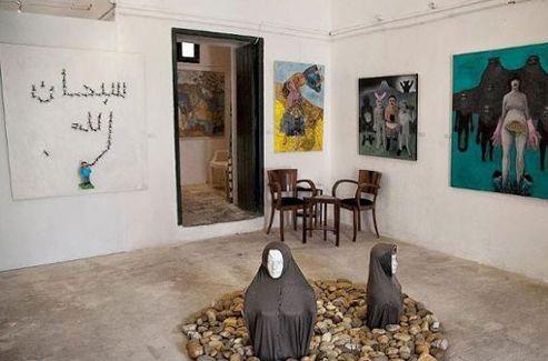 En arrière-plan, des fourmis forment le mot «Bismillah», «au nom d'Allah». Au centre, deux femmes à demi-ensevelies dans un tas de pierres, symboles de la lapidation. (© Wassim Ghozlani)