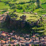 Sertie de coteaux et de toits de tuiles romaines, la forteresse de Polignac est le berceau de l'une des plus anciennes familles de France. Vicomtes du Velay, ses seigneurs entretinrent des relations souvent conflictuelles avec les évêques du Puy.
