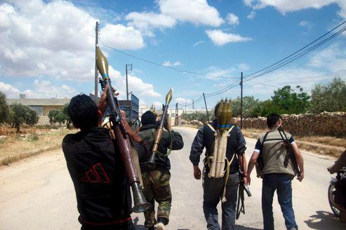 Équipés de lance-roquettes d'origine saoudienne,seules armes capables d'arrêter les chars de l'armée syrienne, des insurgés marchent dans les faubourgs d'Idlib en mai 2012.