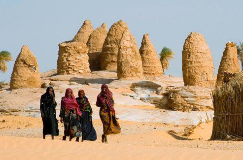 Peu habituées aux visiteurs, les femmes des villages manifestent leur curiosité. Chez elles, les huttes comme les greniers à dattes sont construits avec les matériaux disponibles: la terre et les palmiers.
