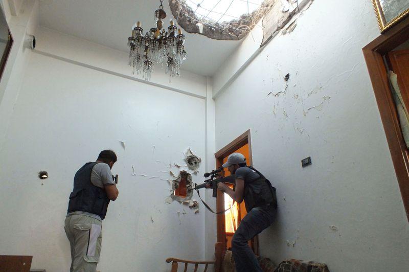 <strong>Fenêtre de tir.</strong> À Homs (notre photo), les combats entre insurgés et forces du régime syrien ont une nouvelle fois ensanglanté les rues. Dans le même temps Damas, la capitale syrienne, était lundi le théâtre de combats d'une rare violence pour la seconde journée consécutive. Les troupes du régime ont lancé une offensive sans précédent pour tenter de reprendre le contrôle de quartiers périphériques de la capitale favorables aux opposants. Selon des militants, toutes les routes reliant Damas à sa province ont été coupées. «Ce sont les premiers combats de ce genre dans la capitale. C'est un tournant dans la révolution syrienne», a affirmé lundi un militant de Damas. <strong></strong>