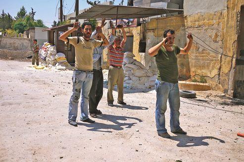 Des hommes fidèles au régime d'Assad, qui s'étaient retranchés à l'intérieur du commissariat d'al-Sharr, à Alep, ont fini par se rendre à la rébellion, mercredi.