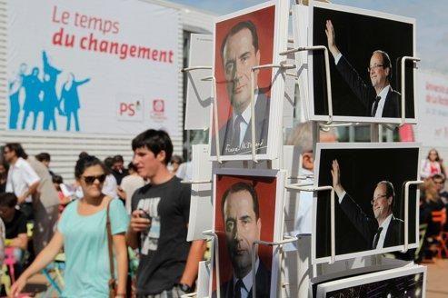 Des gens passent devant un présentoir de cartes postales de François Mitterrand et François Hollande, jeudi, à La Rochelle.