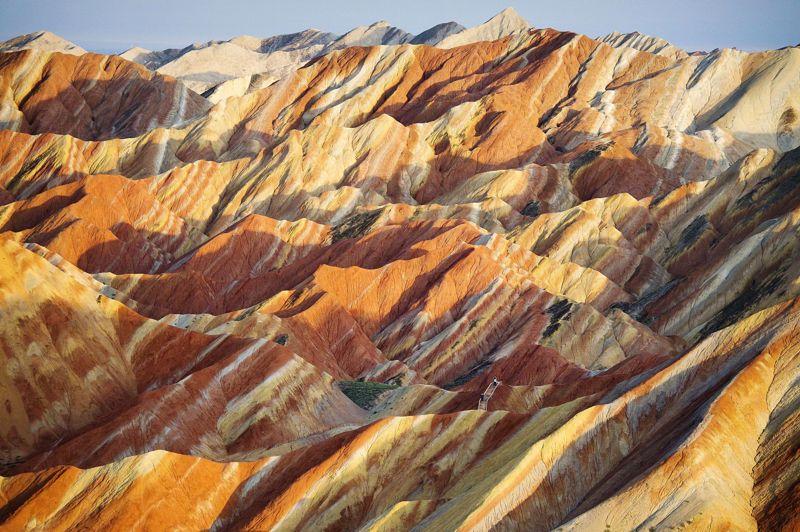 <strong>Sur les falaises de grès.</strong> Comme perdus dans l'immensité de ce paysage minéral, deux promeneurs minuscules (au centre) profitent d'une des plus belles vues au monde. Rien que pour leurs yeux s'étend à l'infini le Parc naturel géologique de Zhangye Danxia, signifiant littéralement «relief nuages pourpres», dans la province chinoise du Gansu. Un ensemble unique de stries et de coulées multicolores provoquées par la lente érosion du grès sous l'action millénaire du gel, du ruissellement et du vent. Ces formations montagneuses n'existent qu'en Chine et ont été classées à ce titre au patrimoine de l'humanité par l'Unesco sous le nom de Danxia de Chine en 2010. Pour l'instant, six sites ont été sélectionnés, sur les quelque 780 découverts dans le pays.