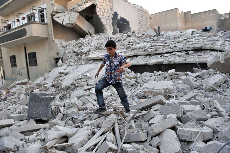 <strong>Raid</strong>. Ce jeune garçon est un rescapé. Il court sur les décombres des bâtiments détruits suite à un raid aérien contre la ville de Maaret al-Noomane, dans le nord-ouest de la Syrie, ce jeudi. Des chasseurs-bombardiers de l'aviation syrienne, avaient survolé la ville rebelle et sa région pendant toute la matinée, faisant de brefs piqués à basse altitude pour larguer une dizaine de bombes, detruisant totalement ou partiellement deux immeubles et une mosquée où se trouvaient de nombreux civils, femmes et enfants. Au moins 44 personnes ont été tuées et 30 autres sont portées disparues. Maaret al-Noomane est ville stratégique car située sur la route reliant Damas à Alep, et a été prise il y a près de deux semaines par les insurgés.