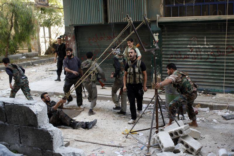 <strong>Poursuite des combats</strong>. Le conflit sanglant en Syrie est entré lundi dans son 20e mois. Alors qu'ici des membres de l'armée de libération syrienne improvisent la fabrication d'une catapulte, à Alep, d'autres combats très intenses ont fait rage lundi, tuant 16 soldats des troupes gouvernementales. L'armée régulière fait face à une multiplication des attaques rebelles contre ses renforts dans la moitié nord de la Syrie. Pour le moment, ni le régime de Bachar al-Assad ni la rébellion n'ont encore réagi à l'appel lancé le même jour par le médiateur international Lakhdar Brahimi pour demander une trêve dans les combats pendant la grande fête musulmane d'Al-Adha fin octobre. Et rien ne permet pour le moment d'espérer un arrêt des hostilités. Selon l'Observatoire syrien des droits de l'Homme, plus de 33.000 personnes ont péri depuis le 15 mars 2011 en Syrie, alors que quelque 340.000 personnes ont pris la fuite dans les pays voisins et environ deux millions ont été déplacées à l'intérieur du pays et ont besoin d'aide selon l'ONU.