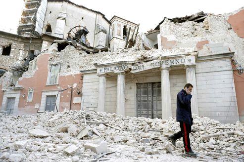 Un militaire italien marche sur les ruines des bâtiments démolis dans le séisme qui a dévasté L'Aquila, en Italie, le 6 avril 2009.