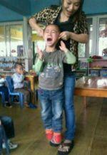 Yan Yanhong soulève un enfant par les oreilles. DR