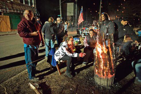 Des résidents sinistrés de Staten Island et des volontaires se réchauffent près d'un brasero de fortune à New Dorp Beach.