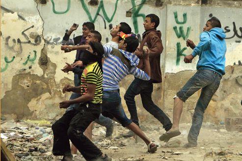 Des jeunes lancent des pierres contre les forces de l'ordre vendredi, lors des manifestations place Tahrir, au Caire.