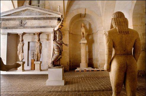 Au premier plan, de dos, l'un des deux kouroi de Delphes. Au centre, une statue d' Athena  et, à l'arrière-plan, la reconstitution de la façade du Trésor de Siphnos.