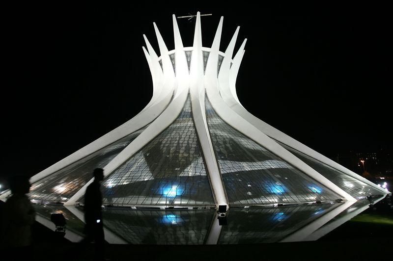 <strong>UNE COURONNE POUR LA CATHÉDRALE DE BRASILIA.</strong> La Catedral Metropolitana Nossa Senhora Aparecida est un des bijoux sculptés par Oscar Niemeyer, pour marquer le futur de sa nation dans la capitale de Brasilia. Les travaux furent achevés en 1958, mais sa consécration date du 31 mai 1970. Cette structure hyperboloïde, d'un diamètre de 70 mètres, est constituée de 16 colonnes de béton qui pèsent, chacune, 90 tonnes, elle représente symboliquement deux mains orantes se rejoignant en direction du ciel. Oscar Niemeyer fut toute sa vie un communiste convaincu, rappellent ses proches. La première structure hyperboloïde est celle du Russe Vladimir Choukhov, à Nijni Novgorod, en 1896. La plus célèbre reste la Tour Choukhov à Moscou, construite par le même Vladimir Choukhov, entre 1920 et 1922 (d'une hauteur de 148,5 mètres à l'origine, surélevée par la suite par de nombreuses antennes, elle culmine à 160 mètres et pèse 220 tonnes). On pénètre dans la Cathédrale Métropolitaine Notre-Dame de l'Apparition de Brasilia, entourée d'un bassin d'eau, par une entrée souterraine, encadrée de quatre statues géantes en bronze du sculpteur Dante Croce représentant les Évangélistes, Matthieu, Marc, Luc sur la gauche et Jean sur la droite. Le toit de la nef est un vitrail composé de 16 teintes de fibre de verre qui dessine un flot divin entre les colonnes de béton. Majesté et symbolisme, modernité et éternité.