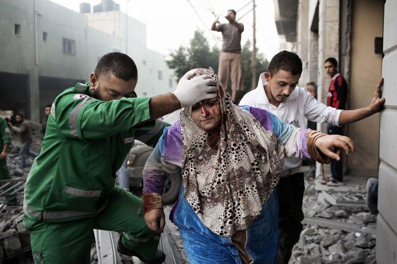 <strong>NOVEMBRE</strong><br/><strong>Gaza</strong>. Deux hommes aident une palestinienne à sortir de son immeuble, endommagé lors d'un raid aérien israélien dans la ville de Gaza, le 19 novembre. Ce conflit d'une durée de huit jours tua plus d'une centaine de personnes, principalement du côté palestinien.
