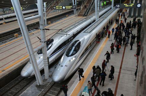 Les journalistes se pressent pour photographier la rame du train à grande vitesse.