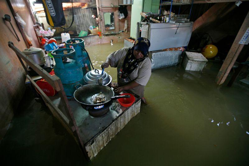 <strong>Eaux profondes.</strong> Comme si de rien n'était, cette Malaisienne prépare le repas, de l'eau jusqu'à la ceinture. L'est du pays est actuellement en proie à de fortes inondations causées par des pluies torrentielles. Une catastrophe aux lourdes conséquences, puisque quelque 20.000 Malaisiens ont été évacués, et selon les autorités locales, deux personnes auraient trouvé la mort.