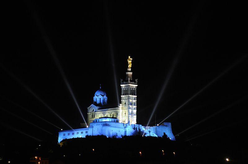 La foule amassée sur le Vieux-Port s'est alors tournée pour admirer la basilique Notre-Dame-de-la-Garde nouvellement illuminée, saluant les variations de couleurs.