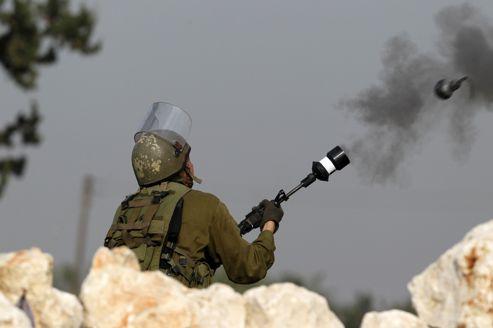 Un soldat israélien tire des gaz lacrymogènes, en janvier 2013, face à des manifestants palestiniens dans le village de Budrus en Cisjordanie.