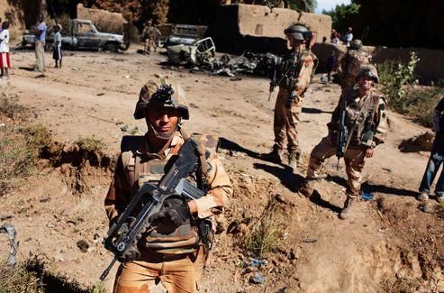 Dans Diabali libérée, des hommes de l'infanterie de marine patrouillent devant les carcasses de pick-up calcinées durant les combats.